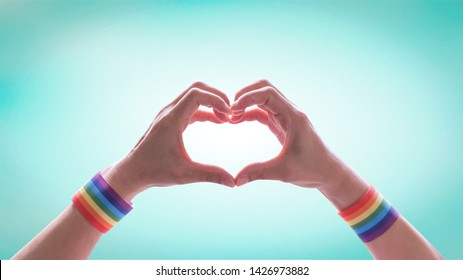 LGBT pride month with rainbow flag ribbon wristband on LGBTQ people heart-shape hands for International day against homophobia and transphobia