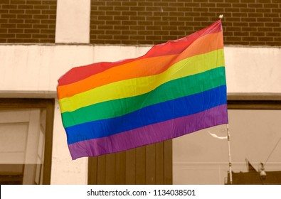 LGBT Rainbow flag isolated from urban background in sepia tone, shallow depth of field