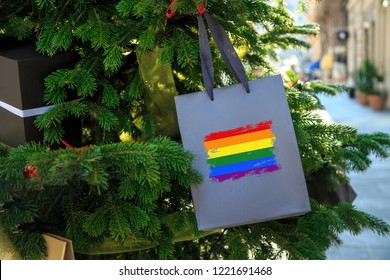 LGBT rainbow flag printed on a Christmas shopping bag. Close up of a shopping bag as a decoration on a Xmas tree on a street . Christmas shopping, local market sale and deals concept.