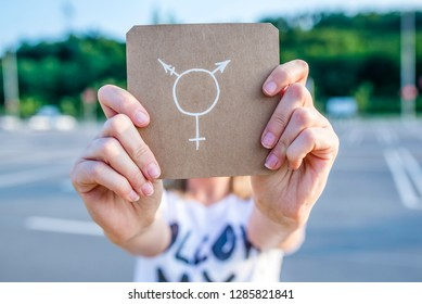 LGBT rights concept. Transgender person coming forward about sexuality orientation. Woman outdoors showing a notepad in front of her with a transgender symbol drawn in it