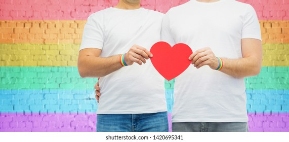 lgbt, same-sex love and homosexual relationships concept - close up of hugging male couple wearing gay pride awareness wristbands holding red heart shape over rainbow colored brick wall background