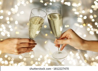 lgbt, same-sex marriage, celebration and love concept - close up of female gay couple hands holding and clinking champagne glasses in bed