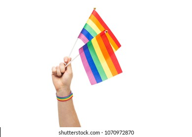 lgbt, same-sex relationships and homosexual concept - close up of male hand wearing gay pride awareness wristband holding rainbow flags