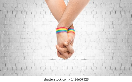 lgbt, same-sex relationships and homosexual concept - close up of male couple wearing gay pride rainbow awareness wristbands holding hands over brick wall background