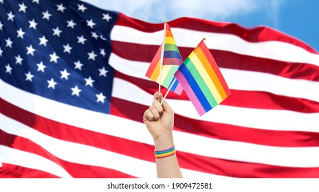 lgbt, same-sex relationships and homosexual concept - close up of male hand wearing gay pride awareness wristband holding rainbow flags over american flag background