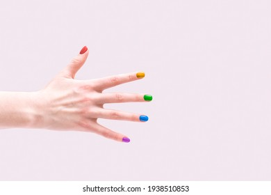 LGBT style manicure. Multi-colored nail polish on female hands.