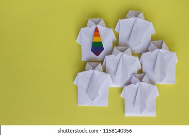 LGBT symbol of rainbow flag on tie. Figures of people, shirt made of paper, origami. Protection of the rights of homosexuals, tolerance. Public opinion. Stand out from the crowd. Gays, transgender.