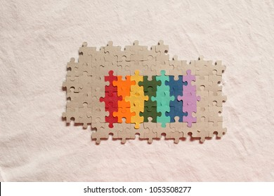 LGBTQ flag colors painted on puzzle pieces