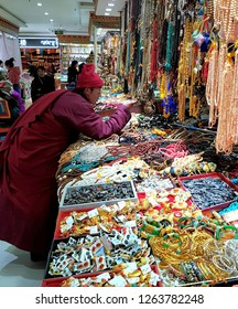 Lhasa, China - December 12 2018: Buddhist monks looking at Tibetan handicrafts in a traditional market on Bohkar street in Lhasa in Tibet, China