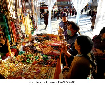 Lhasa, China - December 12 2018:Tibetan Buddhists people looking at prayer wheels in a traditional market on Bohkar street in Lhasa in Tibet, China