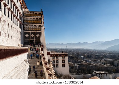 Lhasa, China - December 13 2018: Tourists walk up the stairs leading to the famous Potala Palace in Lhasa old town in Tibet province with the city in the background