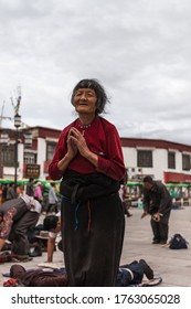 Lhasa, China - June 21, 2012 - Old tibetan woman praying on the square in front of   Jokhang temple, Lhasa, Tibet, China on June 21, 2012