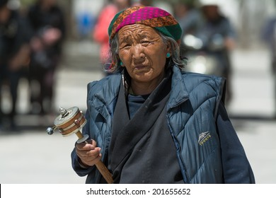 LHASA, CHINA - May 15: Unidentified Tibetan pilgrim circles the Potala palace on May 15, 2014 in Lhasa, China. Devotees walk 3 times around the Potala for good luck.