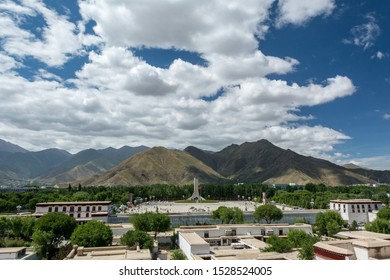 Lhasa, Tibet - 24 JUN 2018: Landscape photo of Potala square in Tibet, Lhasa. With Monument to the Peaceful Liberation of Tibet. Background with blue sunny sky and white clouds.