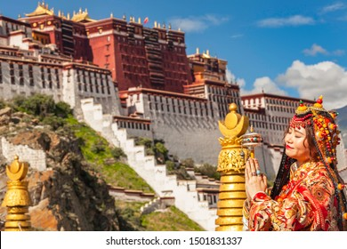 LHASA, TIBET - AUGUST 11, 2019: Tibetan woman in traditional dress   in front of Potala Palace in Lhasa