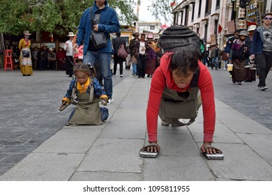 LHASA, TIBET AUTONOMOUS REGION, CHINA - CIRCA MAY 2018: Mother and her daughter on their pilgrimage to Lhasa. They are performing full body prostration during all the way.