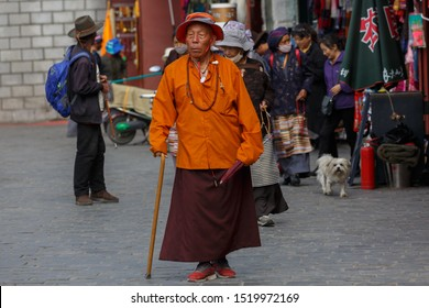LHASA, TIBET / CHINA - Aug 3, 2017: Elderly man with orange jacket and red skirt walking the Kora. He is leaning on a walking stick and holding an umbrella. Barkhor street, near Jokhang temple.