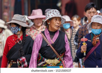 LHASA, TIBET / CHINA - Aug 3, 2017: Elderly woman with colorful cloth at Lhasa's Barkhor Street. She walks the traditional Kora. Encircling the famous Jokhang temple (center of Tibetan Buddhism).