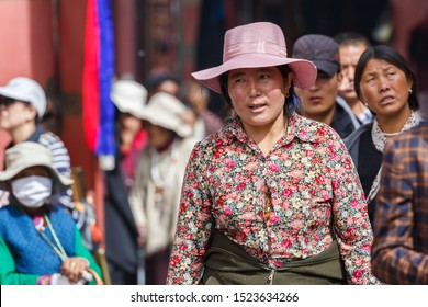 LHASA, TIBET / CHINA - Aug 3, 2017: Woman with pink hat and blouse with flower pattern on Barkhor street. She is walking the Kora around Jokhang temple - many other pilgrims are in the background.