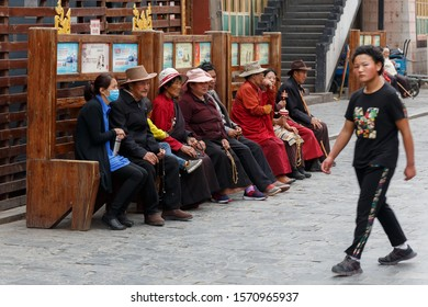 LHASA, TIBET / CHINA - August 1, 2017: Pilgrims taking a rest on a bench - close to Barkhor street and Jokhang temple. Believers in tibetan buddhism. Dressed in traditional cloths with prayer beads.