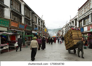 Lhasa, Tibet / China - August 20, 2012: the Barkhor street scene of Lhasa city. A group tibetan pilgrims walking on Barkhor street. They are holding prayer beads and hand prayer wheels.