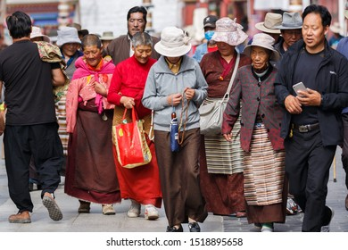 "LHASA, TIBET / CHINA - August 3, 2017: Group of pilgrims doing the traditional ""Kora"" on Barkhor street. The ""Barkhor Kora"" is performed by making a circumambulation around the famous Jokhang temple."