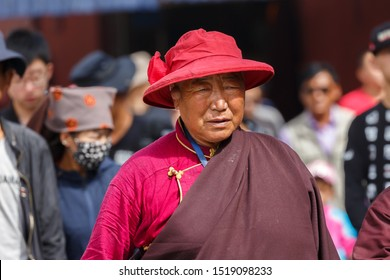 LHASA, TIBET / CHINA - August 3, 2017: Old man with red hat and rope at Barkhor street. Doing the traditional Kora (walk around Jokhang temple). Numerous pilgrims walk the Kora every day.
