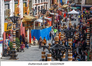 LHASA, TIBET / CHINA - August 3, 2017: Taking a deeper look into Barkhor street: colorful buildings and pilgrims walking the Kora. Just around the corner is Jokhang temple (Unesco World Heritage).