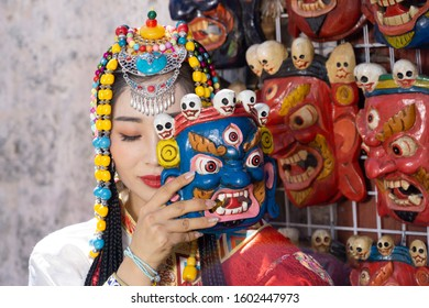 Lhasa, Tibet, China, Chengguan District, June 23 2019: closeup of beautiful young make up girl wearing traditional Tibetan clothes and jewelry, while he is trying on a traditional mask