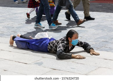 """LHASA, TIBET / CHINA - Jul 30, 2017: Female pilgrim lying on the floor after prostrating herself. Doing the """"Barkhor Kora"""", A devotional pilgrim circuit around the exterior of the old Jokhang Temple."""