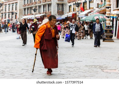 LHASA, TIBET / CHINA - July 30, 2017: Elderly, buddhist pilgrim in orange and red robe with walking stick on Barkhor street. In the background tourists and typical tibetan buildings. Devotion, Kora.