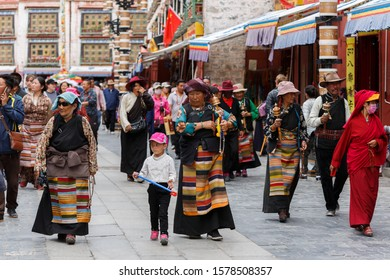 LHASA, TIBET / CHINA - July 30, 2017: A group tibetan pilgrims walking on Barkhor street. They are holding prayer beads and hand prayer wheels.  Walking around the sacred Jokhang temple.