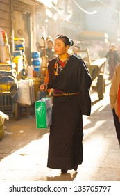 Lhasa, Tibet, China - October 17, 2007: A modern beautiful young Tibetan woman wearing traditional brown clothes walking the Barkhor on a backlit morning alleyway