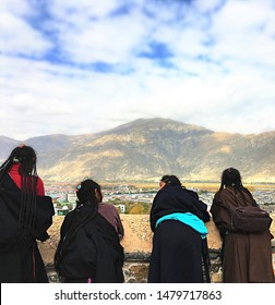 Lhasa, Tibet / China - October 19 2016: Four Tibetan girls look at the view of Lhasa from the Potala Palace.