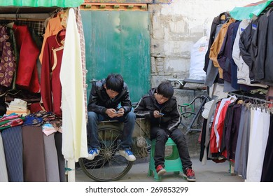 LHASA, TIBET, CHINA - OCTOBER 19: Non-tibetan han people youngsters play with e-game devices-rear part of street shop on the Kora-circumambulation circuit on October 19, 2012. Lhasa city-Tibet-China.