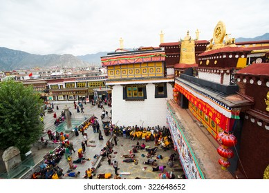 LHASA, TIBET, CHINA - SEPTEMBER 12, 2015: Pilgrims and locals are praying in front of Jokhang Temple in Lhasa, Tibet, China. This temple is the most sacred and important temple in Tibet.