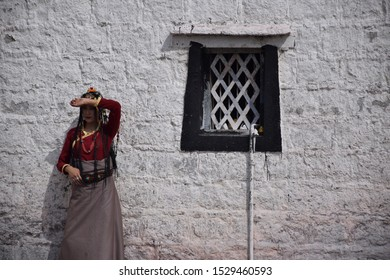 LHASA, TIBET, CHINA - SEPTEMBER 30 - Beautiful asian girl takes photo shoot dressed with traditional tibetan clothes nearby Jokhang temple on september 30, 2019 in Lhasa