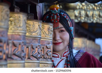 LHASA, TIBET, CHINA - SEPTEMBER 30 - Beautiful asian girl takes photo shoot dressed with traditional tibetan clothes nearby prayer wheels on september 30, 2019 in Lhasa