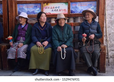 LHASA, TIBET, CHINA - SEPTEMBER 30 - Old tibetan people in traditional clothes sit on a bench nearby Jokhang temple on september 30, 2019 in Lhasa