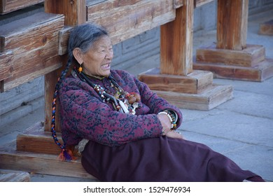 LHASA, TIBET, CHINA - SEPTEMBER 30 - Old tibetan woman in traditional clothes sits on the street nearby Jokhang temple on september 30, 2019 in Lhasa
