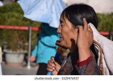 LHASA, TIBET, CHINA - SEPTEMBER 30 - Old tibetan woman in traditional clothes nearby Jokhang temple on september 30, 2019 in Lhasa