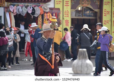 LHASA, TIBET, CHINA - SEPTEMBER 30 - Old tibetan man in traditional clothes pray with his prayer wheel nearby Jokhang temple on september 30, 2019 in Lhasa