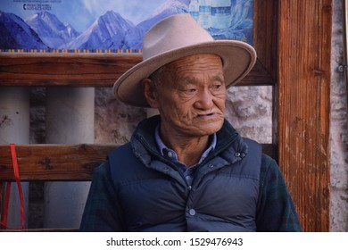 LHASA, TIBET, CHINA - SEPTEMBER 30 - Old tibetan man sits on a bench nearby Jokhang temple on september 30, 2019 in Lhasa