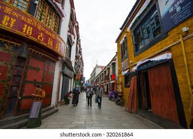 LHASA, TIBET, CHINA-SEPTEMBER 13, 2015: Tibetan people walk in street and pray in Lhasa, Tibet. Most Tibetans generally observe Tibetan Buddhism.