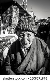 Lhasa, Tibet- February 2 2008: Portrait in black and white of a traditional tibetan old woman walking in the streets of Lhasa, Tibet.