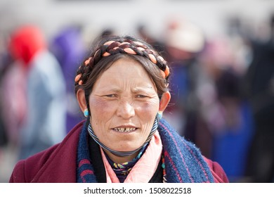 Lhasa, Tibet - January 29, 2019: A Khampa woman, donning traditional plaits and jewelry, walks the kora (a type of Buddhist pilgrimage) around the Jokhang temple in Lhasa.