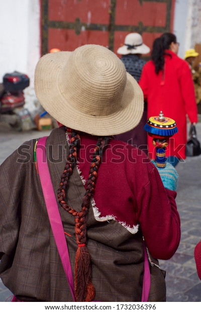 Lhasa, Tibet - People's Republic of China - 2018: A woman with braided hair spins a prayer wheel while wearing a hat in the Tibetan capital