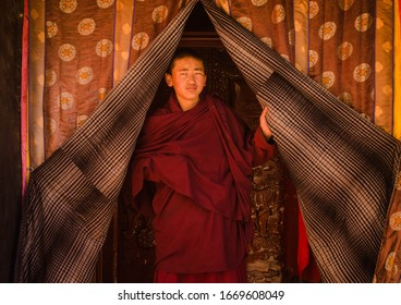 Lhasa, Tibet/China- October 20 2019: Portrait of a young Tibetan monk wearing traditional red robes and opening traditional Tibetan curtains.