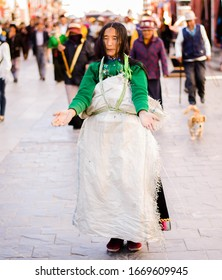 Lhasa, Tibet/China- October 20 2019: Portrait of a Tibetan woman wearing traditional clothing and praying outside Potala Palace in Tibet. Worshipers prostrate themselves in Tibet.