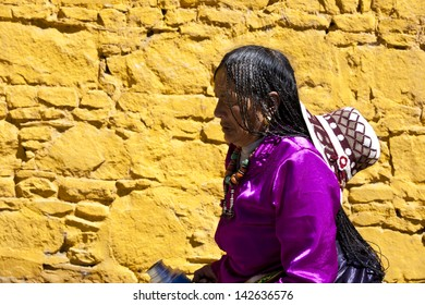 LHASA, TIBET-OCTOBER 07: A Tibetan woman wearing traditional clothes is passing a yellow wall st Sera Monastery on October 07, 2011 in Lhasa, Tibet.